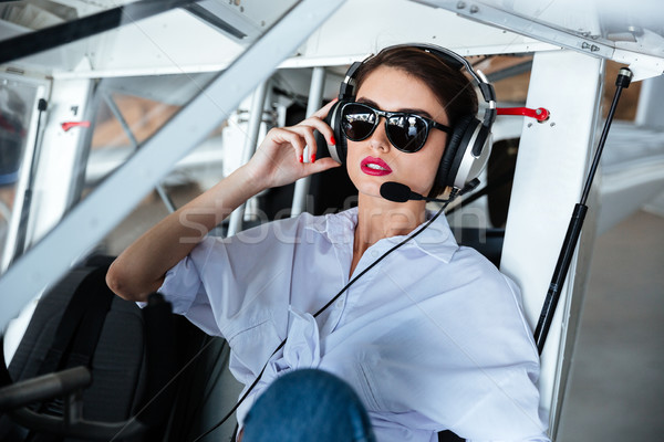 Attractive woman pilot in sunglasses and headset sitting in aircraft Stock photo © deandrobot