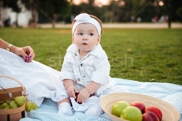 Cute little girl sitting and hiding red apple on picnic Stock photo © deandrobot