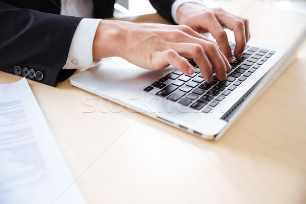 Kezek fiatal üzletember laptopot használ asztal közelkép Stock fotó © deandrobot