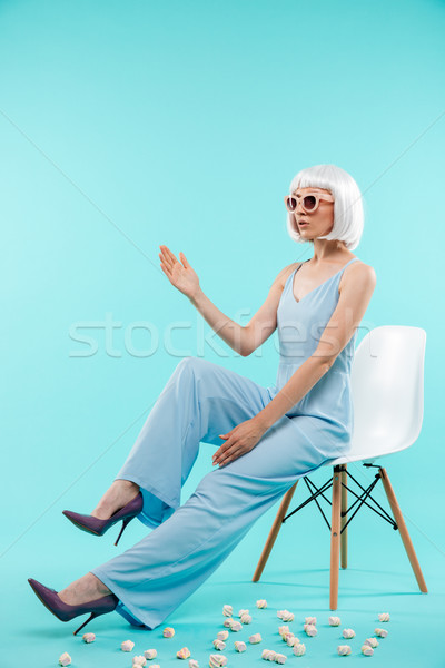 Full length of blonde young woman sitting and pretending robot Stock photo © deandrobot