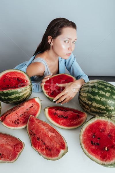 Cute young woman sitting at the table and holding watermelons Stock photo © deandrobot