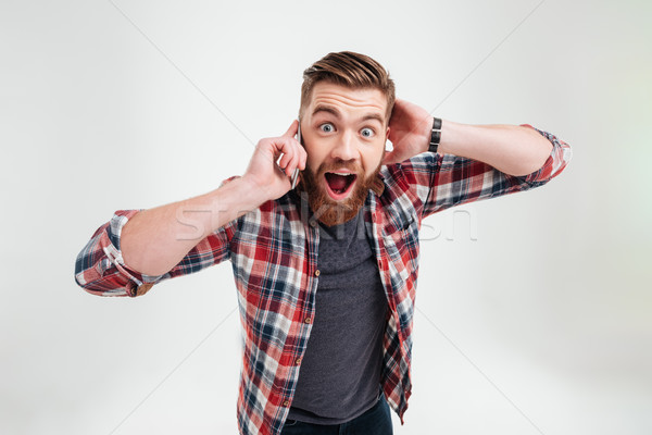 Casual surprised man in plaid shirt talking on mobile phone Stock photo © deandrobot