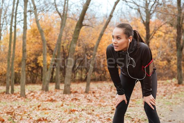 Fiatal hölgy futó meleg ruházat fülhallgató Stock fotó © deandrobot