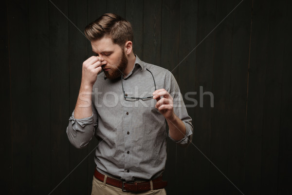 Portrait of a tired exhausted bearded man holding glasses Stock photo © deandrobot