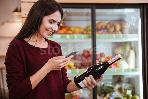 Nő választ bor vonalkód üveg mosolyog Stock fotó © deandrobot