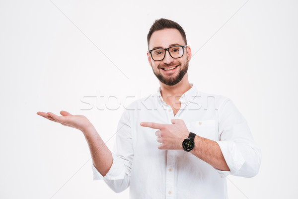 Happy young bearded man holding copyspace and pointing Stock photo © deandrobot