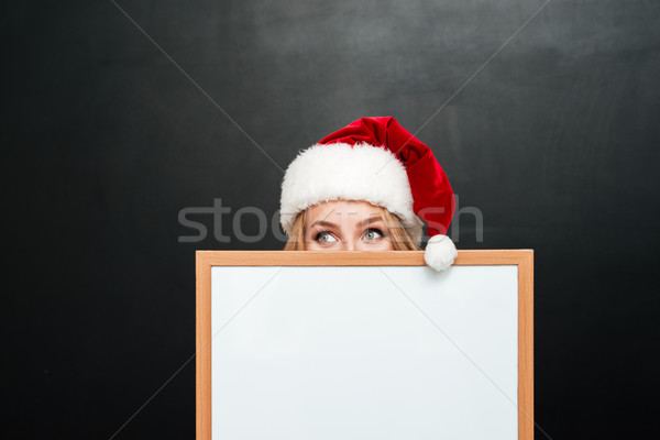 Stock photo: Girl in santa claus hat hiding behind blank white board