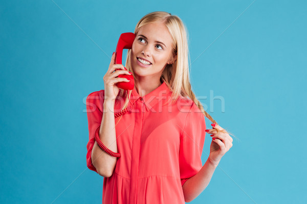 Wondering woman in red dress talking on mobile phone Stock photo © deandrobot