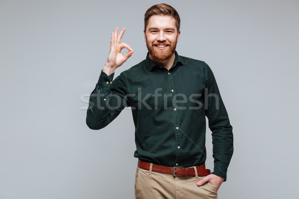 Smiling Bearded man in shirt showing ok sign Stock photo © deandrobot