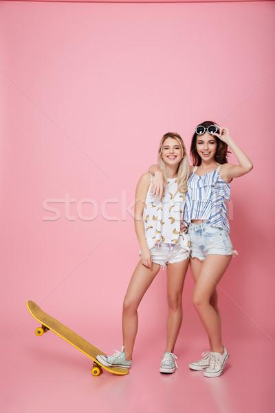 Dos feliz las mujeres jóvenes skateboard pie sonriendo Foto stock © deandrobot