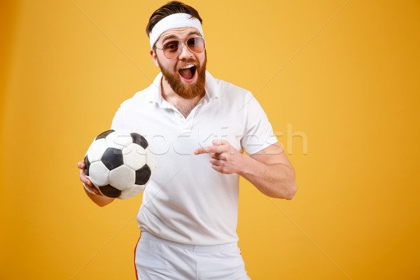 Happy sportsman in sunglasses holding soccer ball Stock photo © deandrobot