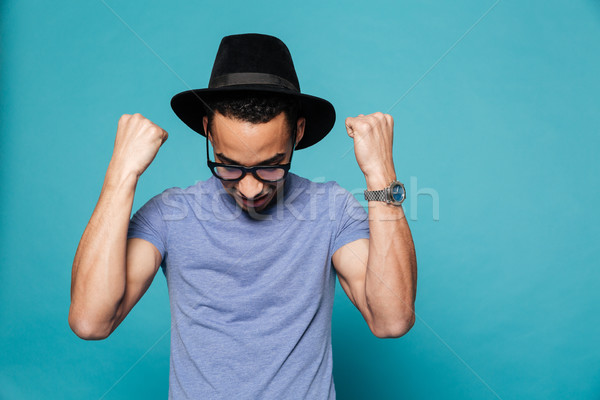 Portrait of casual african american man in hat celebrating success Stock photo © deandrobot