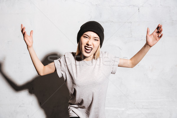 Mad aggressive young woman with black lipstick standing and shouting Stock photo © deandrobot