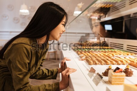 Cheerful young woman standing in supermarket choosing sweeties. Stock photo © deandrobot