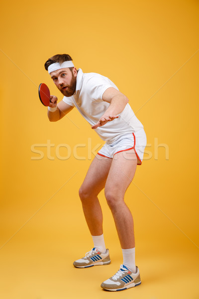 Young sportsman holding racket for table tennis. Stock photo © deandrobot