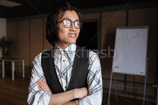 Cheerful young asian man standing with arms crossed Stock photo © deandrobot
