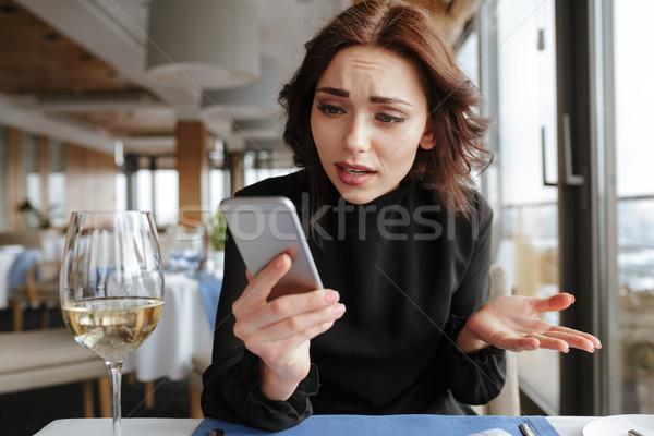 Niezadowolony kobieta restauracji patrząc telefonu sukienka Zdjęcia stock © deandrobot