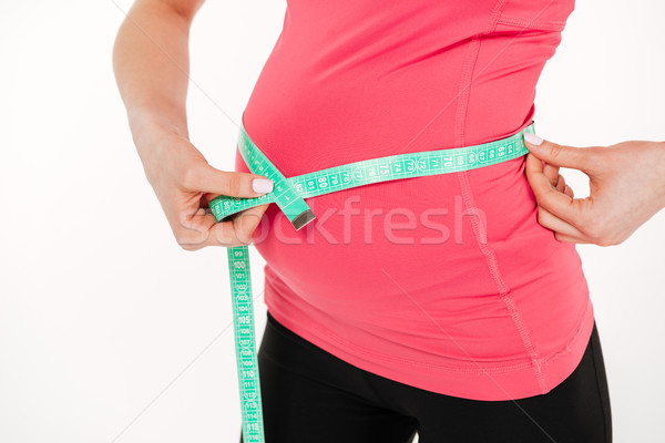 Cropped image of pregnant fitness woman measurement her tummy Stock photo © deandrobot