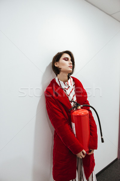 Woman standing and holding fire extinguisher in corridor Stock photo © deandrobot