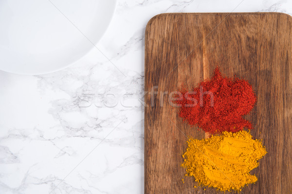Top view of two turmeric and paprika heaps over wooden Stock photo © deandrobot