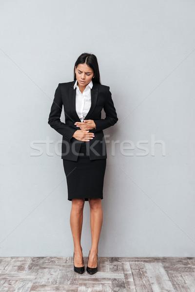 Verticale immagine donna d'affari addominale dolore suit Foto d'archivio © deandrobot
