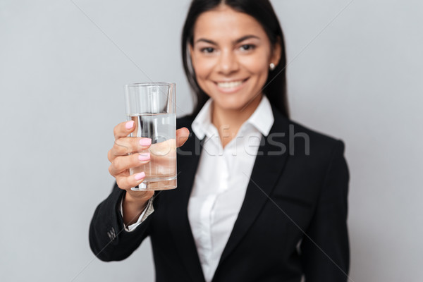 Smiling attractive business woman holding glass of mineral water Stock photo © deandrobot
