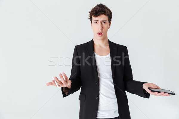 Shocked  Man in suit holding cigarette and  smartphone Stock photo © deandrobot