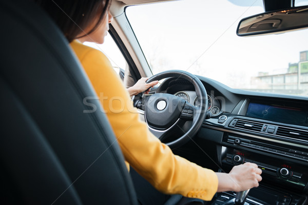 Back view of attractive young woman looking on the road while driving a car Stock photo © deandrobot