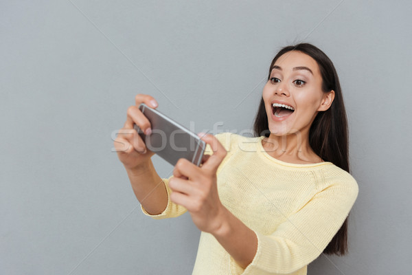Gelukkig opgewonden jonge vrouw spelen video games mobiele telefoon Stockfoto © deandrobot
