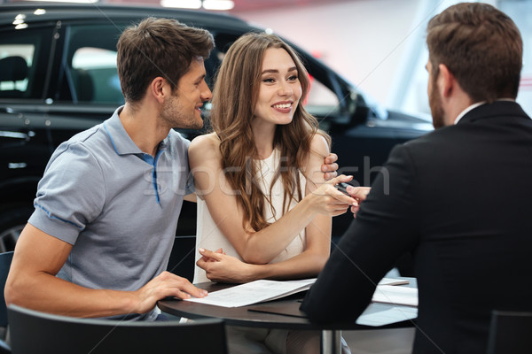 Confident young salesman explaining all the new car features Stock photo © deandrobot