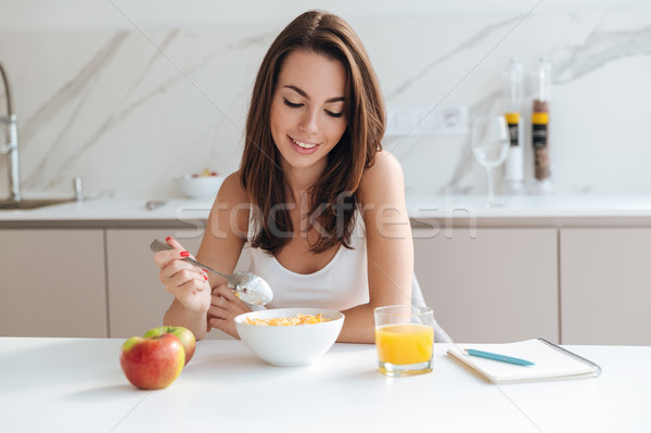 Attractive smiling woman eating corn flakes cereal for breakfast Stock photo © deandrobot