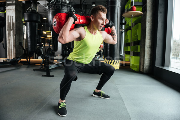 Young concentrated sportsman make sport exercises Stock photo © deandrobot