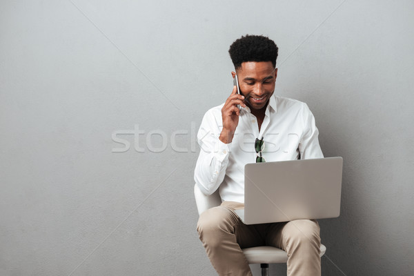 Attractive young african man holding laptop computer on his lap Stock photo © deandrobot