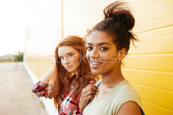 Happy women friends standing over yellow wall. Stock photo © deandrobot