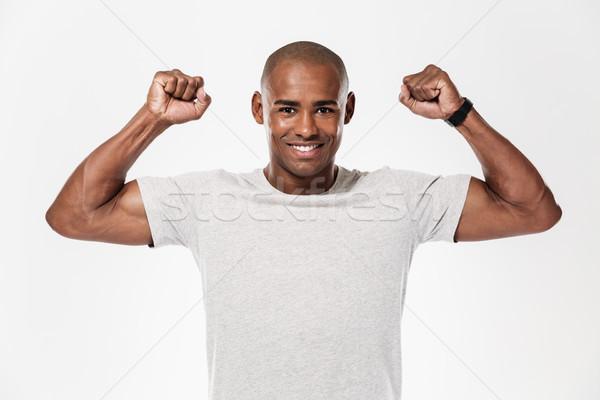 Knap jonge afrikaanse man tonen biceps Stockfoto © deandrobot