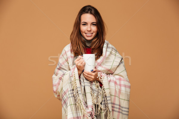 Cheerful young brunette woman covered in plaid, holding cup of h Stock photo © deandrobot