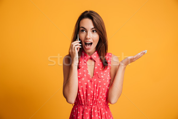 Surprised happy brunette woman in dress talking by the smartphone Stock photo © deandrobot