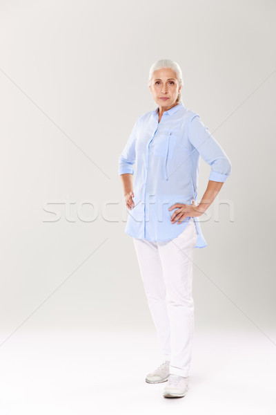Full-length portrait of serious old lady in blue shirt and white Stock photo © deandrobot