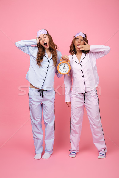 Yawning friends women in pajamas holding alarm clock Stock photo © deandrobot