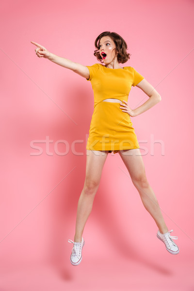 Full length portrait of shocked charming brunette woman with han Stock photo © deandrobot