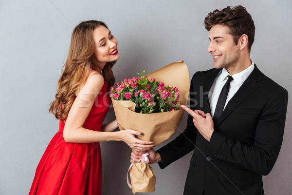 Portrait of a cheerful man giving his girlfriend flower bouquet Stock photo © deandrobot