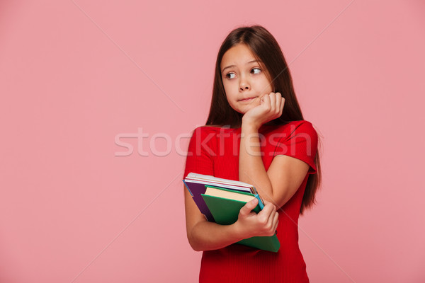 Pensive girl pupil holding books and looking aside over pink Stock photo © deandrobot