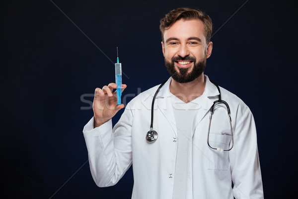Portrait of a smiling male doctor dressed in uniform Stock photo © deandrobot