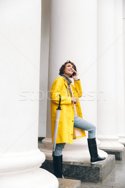 Smiling young woman talking by mobile phone. Looking aside. Stock photo © deandrobot