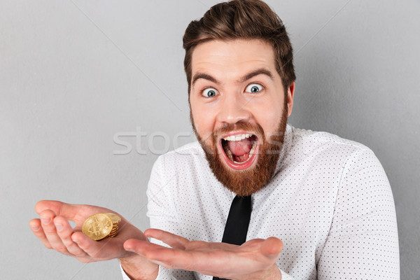 Portrait of an excited businessman showing golden bitcoins Stock photo © deandrobot