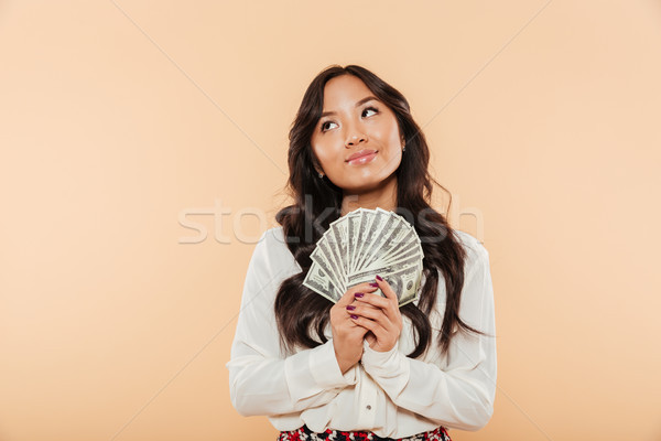 Portrait of brunette asian female looking up while holding fan o Stock photo © deandrobot