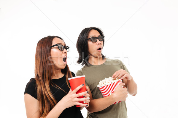 Portrait of a shocked excited asian couple in 3d glasses Stock photo © deandrobot