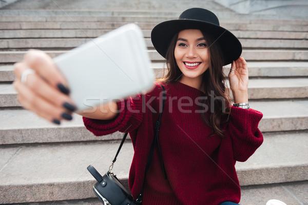 Felice bruna donna Hat maglione seduta Foto d'archivio © deandrobot
