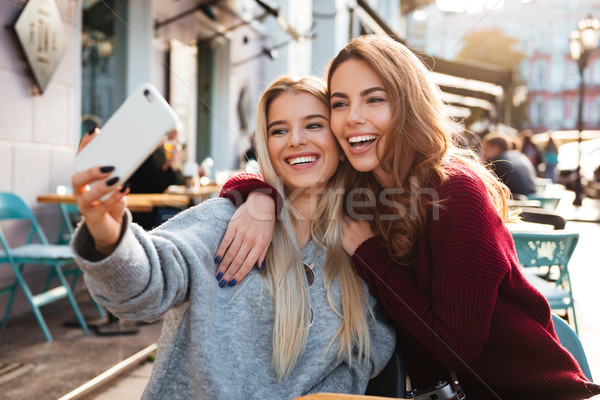 Two happy smiling girls taking a selfie Stock photo © deandrobot