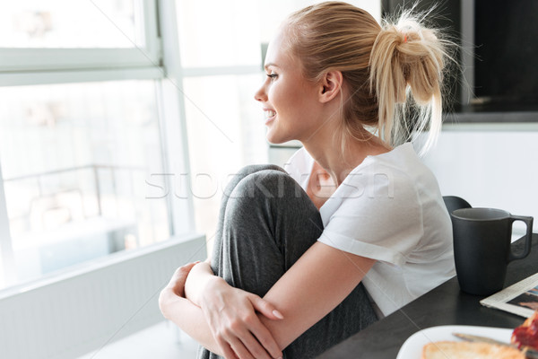 Side view of pretty lady looking aside and smiling Stock photo © deandrobot